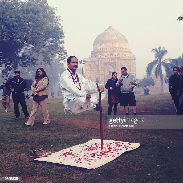 Deepak Sharma claiming to use magic appears to levitate as passers by look on at Lodhi gardens on November 24 2012 in Delhi India