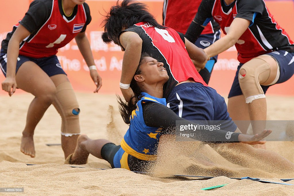 Deepika Sanjeewani Pawith Wanasinghe Mudiyanselage (C) of Sri Lanka is tackled as he competes during the Beach Kabaddi Women's Team Group A match between Thailand and Sri Lanka on Day 4 of the 3rd Asian Beach Games Haiyang 2012 at Fengxiang Beach on June 20, 2012 in Haiyang, China.