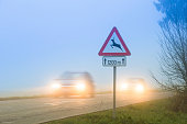 Cars pasing a traffic sign for deer crossing in fog