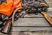 Deer hunting background with hunting gear and apparel on a rustic wooden background with copy space.