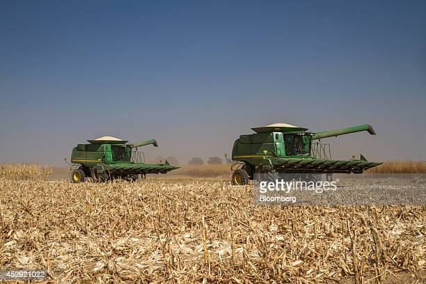 Deere Co 9770 STS combine harvesters drive white corn grain across a harvested field on a farm in Grootvlei South Africa on Tuesday July 29 2014 Meal...