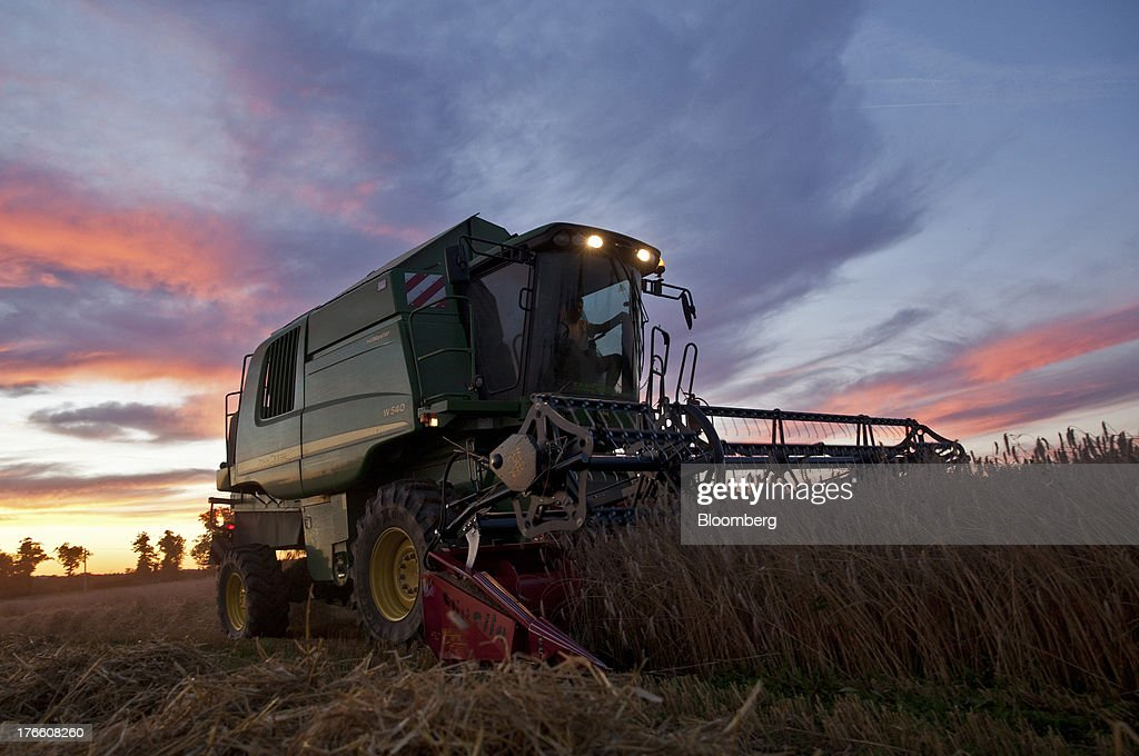 A Deere & Co. John Deere W540 combine harvester gathers crops in a field of triticale wheat as the sun sets in Falguieres, southwest France, on Thursday, Aug. 15, 2013. French farmers harvested better-quality wheat than expected north and east of Paris, making up for low protein content in the southwest and raising confidence the grain will meet export requirements. Photographer: Balint Porneczi/Bloomberg via Getty Images