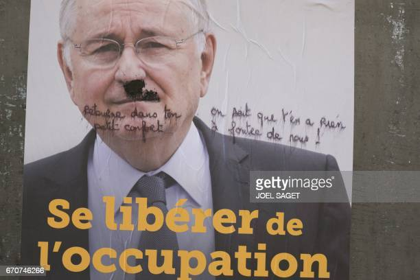 A defaced campaign poster of French presidential election candidate for the Solidarite et Progres party Jacques Cheminade is pictured on April 19...