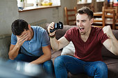 Ecstatic gameplayer expressing triumph with his defeated friend near by