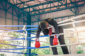 Defeated Asian businessman in suit with boxing in red gloves on boxing ring