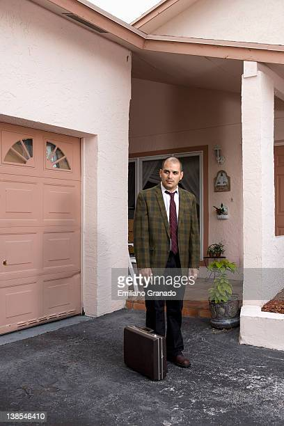 A defeated looking businessman standing in his driveway