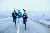 Athlete fitness friends running on an open road.