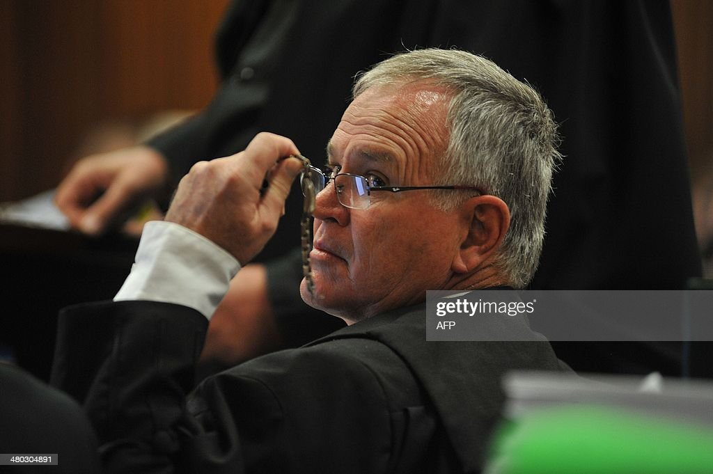 Defence lawyer Barry Roux displays a watch of a witness to some of his team members during South African Paralympic athlete Oscar Pistorius' ongoing murder trial on March 24, 2014 in Pretoria. The murder trial of Paralympian Oscar Pistorius for shooting dead his model girlfriend will extend weeks longer than expected, with a long list of prosecution and defence witnesses yet to take the stand. The trial was supposed to have wrapped up by now, but a court statement on Sunday said the highly-publicised hearings could extend as late as May 16.