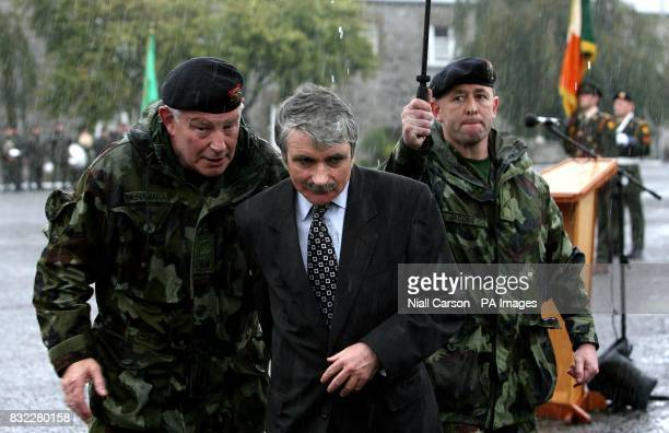 Defence Minister Willie O'Dea runs for cover during heavy rainfall as he reviews the 33rd Infantry Group bound for overseas service with Kosovo Force...