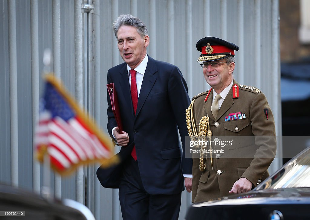 Defence Secretary Philip Hammond (L) passes US Vice President Joe Biden's car as he walks in Downing Street with Chief of the Defence Staff General Sir David Richards on February 5, 2013 in London, England. The Vice President has also met with German and French leaders during his visit to Europe.