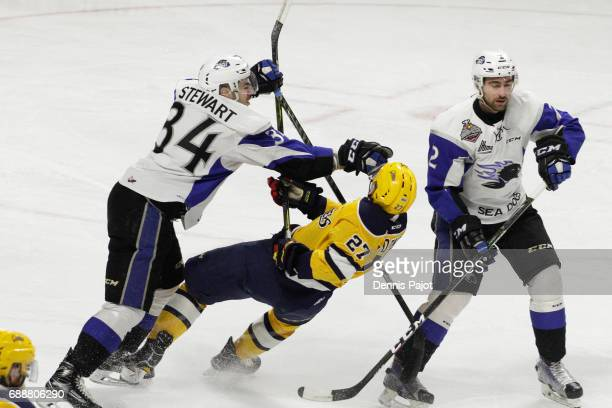 Defenceman Chase Stewart of the Saint John Sea Dogs places a hit against forward Ivan Lodnia of the Erie Otters on May 26 2017 during the semifinal...