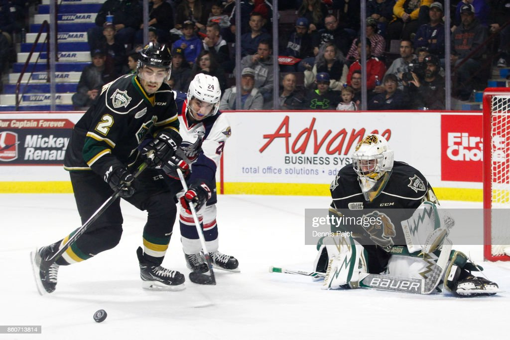 Defenceman Evan Bouchard #2 of the London Knights clears the puck against forward Mathew MacDougall #24 of the Windsor Spitfires on October 12, 2017 at the WFCU Centre in Windsor, Ontario, Canada.