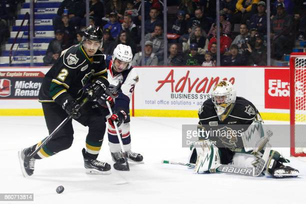 Defenceman Evan Bouchard of the London Knights clears the puck against forward Mathew MacDougall of the Windsor Spitfires on October 12 2017 at the...
