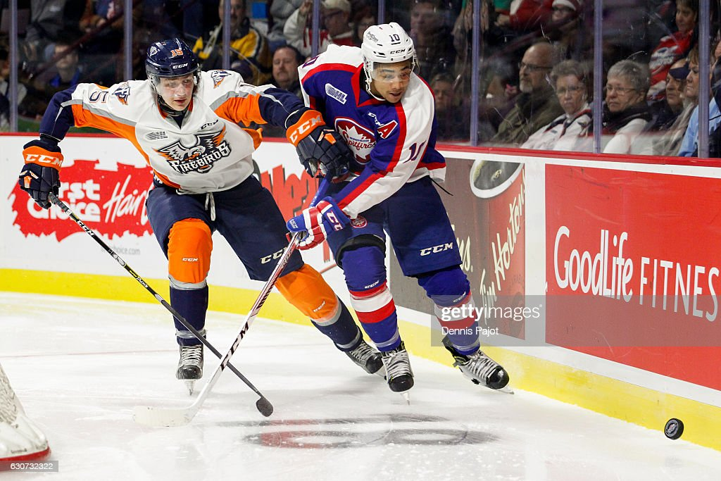 Defenceman Fedor Gordeev #15 of the Flint Firebirds battles for the puck against forward Jeremiah Addison #10 of the Windsor Spitfires on December 31, 2016 at the WFCU Centre in Windsor, Ontario, Canada.