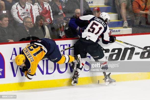 Defenceman Jalen Chatfield of the Windsor Spitfires places a hit against forward Alex DeBrincat of the Erie Otters on May 24 2017 during Game 6 of...