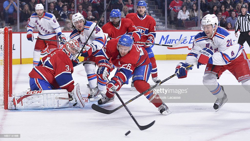 Defenceman <a gi-track='captionPersonalityLinkClicked' href=/galleries/search?phrase=Josh+Gorges&family=editorial&specificpeople=550446 ng-click='$event.stopPropagation()'>Josh Gorges</a> #26 of the Montreal Canadiens clears a loose puck away from <a gi-track='captionPersonalityLinkClicked' href=/galleries/search?phrase=Derek+Stepan&family=editorial&specificpeople=4687181 ng-click='$event.stopPropagation()'>Derek Stepan</a> #21 of the New York Rangers as goalie <a gi-track='captionPersonalityLinkClicked' href=/galleries/search?phrase=Carey+Price&family=editorial&specificpeople=2222083 ng-click='$event.stopPropagation()'>Carey Price</a> #31 looks on during the NHL game on March 30, 2013 at the Bell Centre in Montreal, Quebec, Canada.