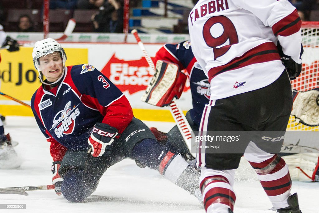 Defenceman Liam Murray #3 of the Windsor Spitfires stands in front of a shot by forward Robby Fabbri #9 of the Guelph Storm on March 12, 2015 at the WFCU Centre in Windsor, Ontario, Canada.