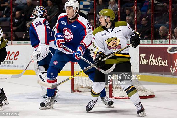 Defenceman Logan Stanley of the Windsor Spitfires battles in front of the net against forward Steve Harland of the North Bay Battalion on March 5...