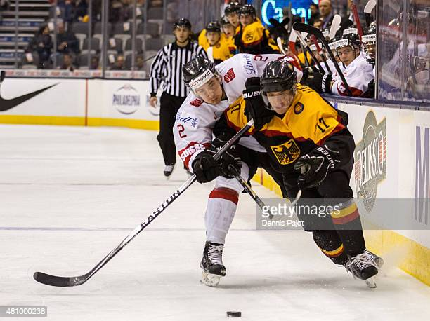 Defenceman Michael Fora of Switzerland battles for the puck against forward Frederik Tiffels of Germany during the 2015 IIHF World Junior...