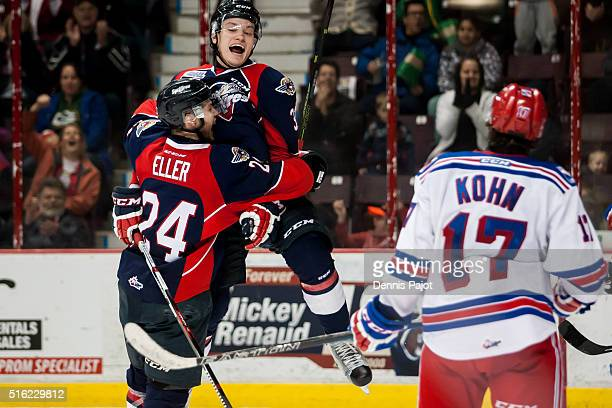 Defenceman Mikhail Sergachev of the Windsor Spitfires celebrates with teammate forward Mads Eller after a goal against the Kitchener Rangers on March...