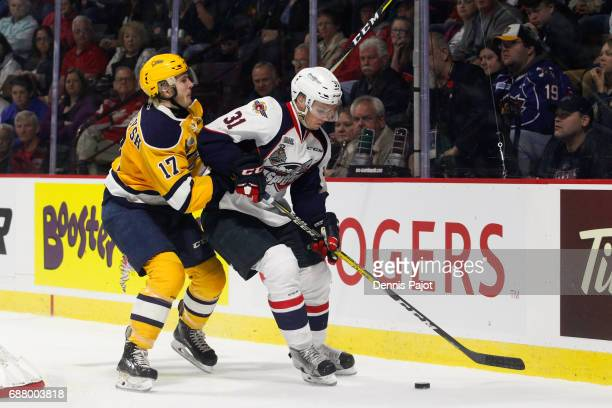 Defenceman Mikhail Sergachev of the Windsor Spitfires moves the puck against forward Taylor Raddysh of the Erie Otters on May 24 2017 during Game 6...