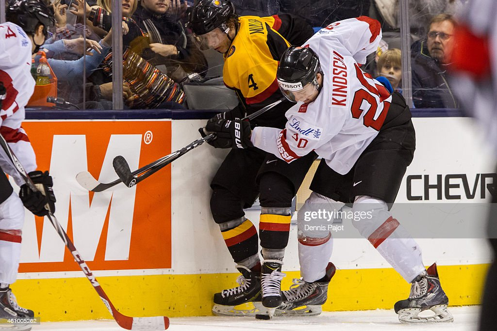 Defenceman Simon Kindschi #20 of Switzerland battles for the puck against defenceman Jonas Muller #4 of Germany during the 2015 IIHF World Junior Championship on January 03, 2015 at the Air Canada Centre in Toronto, Ontario, Canada.