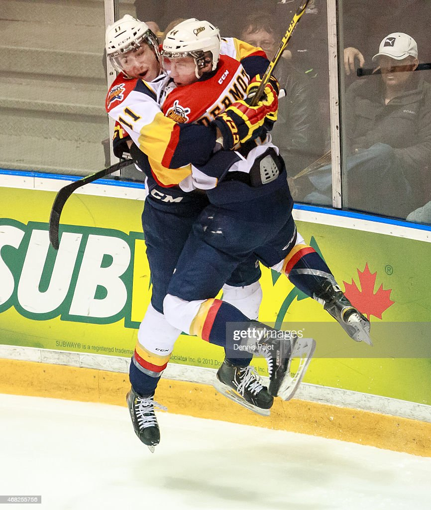 Defenceman Travis Dermott and forward Mason Marchment of the Erie Otters celebrate a goal against the Sarnia Sting during Game Four of the Western...