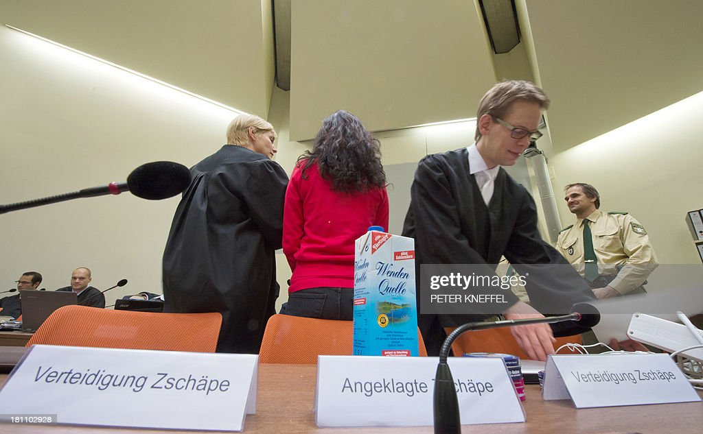 Defendant Beate Zschaepe (C) turns her back as she stands between her lawyers Anja Sturm (L) and Wolfgang Heer (R) in the courtroom in Munich, southern Germany, on September 19, 2013. Zschaepe, alleged member of the farright National Socialist Underground (NSU), is charged with complicity in the murders of eight ethnic Turks, a Greek immigrant and a German policewoman between 2000 and 2007. AFP PHOTO / DPA/ PETER KNEFFEL OUT