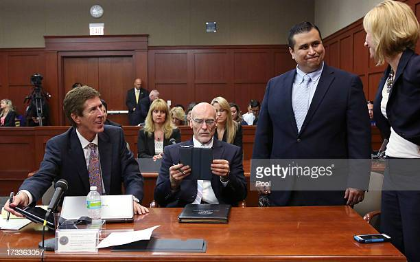 Defendant George Zimmerman smiles while standing with his attorneys Mark O' Mara Don West and Lorna Truett during his murder trial July 12 2013 in...