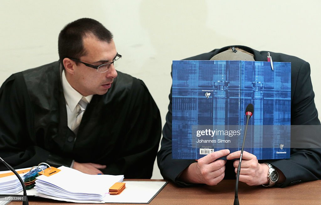 Defendant Holger G. (R) hides behind a file prior to the trial during day 18 of the NSU neo-Nazis murder trial at the Oberlandgericht Muenchen court on July 3, 2013 in Munich, Germany. Beate Zschaepe is the main defendant and is on trial for her role in assisting Uwe Boehnhardt and Uwe Mundlos in the murder of nine immigrants and one policewoman across Germany between 2000 and 2007. Together the trio called themselves the NSU, or National Socialist Underground, and were able to operate unbeknownst to police until Mundlos and Boehnhardt were cornered in 2011 after the two robbed a bank. Four other co-defendants, including Ralf Wohlleben, Holder G., Carsten S. and Andre E., are accused of assisting the trio. Carsten S. and Holger G. have declared themselves willing to give limited testimonies, while Zschaepe has thus far remained silent and refuses to answer any questions by the court.