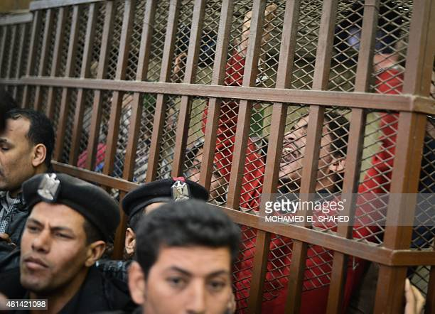 Defendants react behind the bars at a court in Cairo following the acquittal on January 12 2015 of 26 male men accused of 'debauchery' after they...