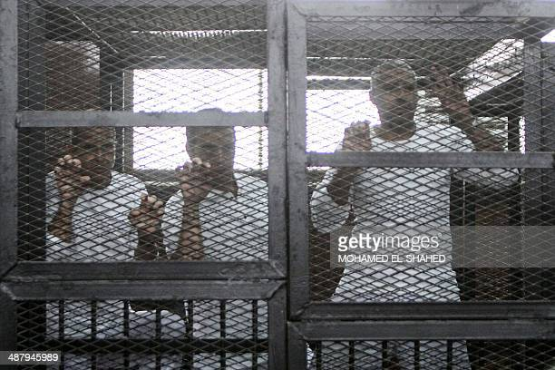 Defendents who are in custody stand in the accused cells during the trial of 20 individuals including five AlJazeera journalists for allegedly...