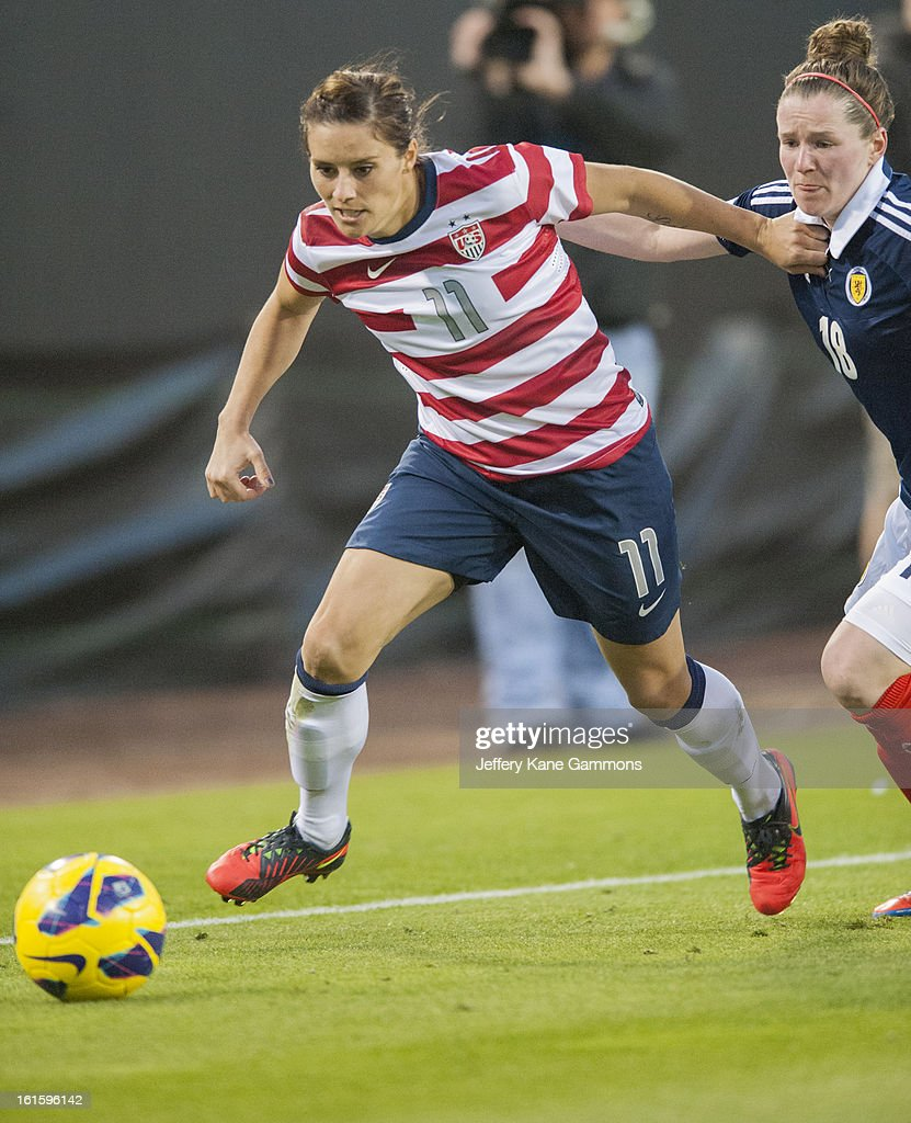 Defender Ali Krieger #11 of the United States fights past Forward Emma Mitchell #18 of Scotland during the game at EverBank Field on February 9, 2013 in Jacksonville, Florida.