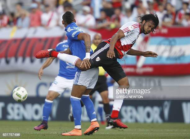 Defender Arturo Mina of Argentine club River Plate challenges forward Ayrton Del Valle of Colombian team Millonarios FC for the ball during their...