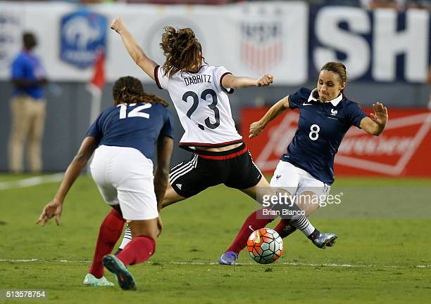 Defender Jessica Houara of France and midfielder Elodie Thomis protect the ball from Germany midfielder Sara Dabritz of Germany during the second...
