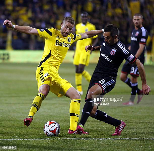 Defender Josh Williams of the Columbus Crew fights for the ball with midfielder Davy Arnaud of DC United during the second half of their game at...