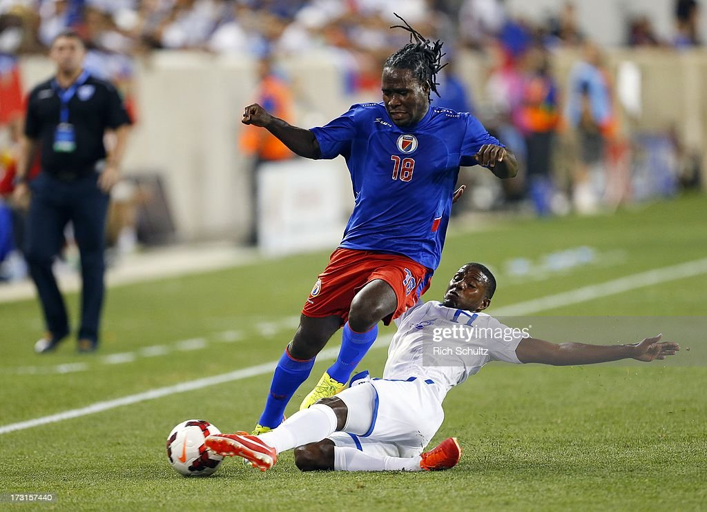 Defender Juan Carlos Garcia #6 of Honduras makes a slid tackle on a ball controlled by forward Leonel Saint Preux #18 of Haiti during the first half of a 2013 CONCACAF Gold Cup soccer match on July 8, 2013 at Red Bull Arena in Harrison, New Jersey. Honduras defeated Haiti 2-0.