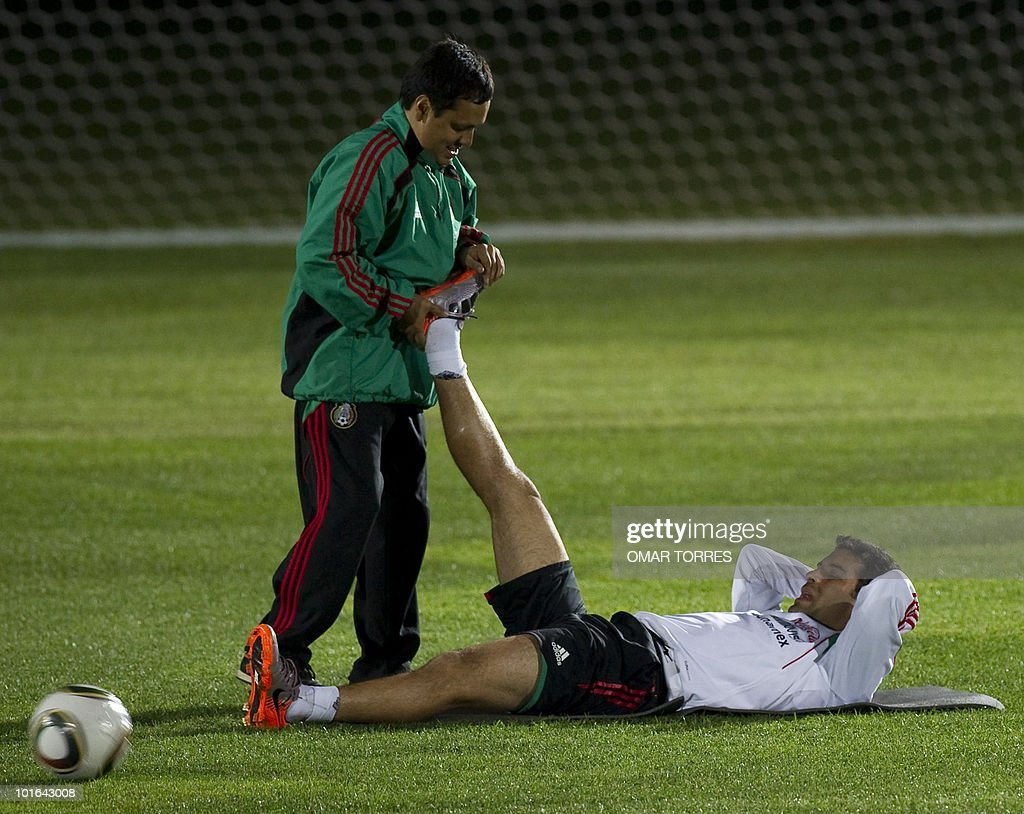 Defender Rafael Marquez, of the Mexican national team, is helped by an assitant to stretch his legs during a training session at the Waterstone College in Johannesburg on June 5, 2010. Mexico will kick off the four-yearly tournament next Friday against host South Africa. AFP PHOTO/Omar TORRES