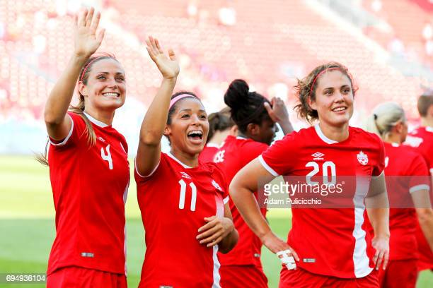 Defender Shelina Zadorsky of Team Canada and teammates Midfielder Desiree Scott and Defender Shannon Woeller smile and wave to the crowd after...