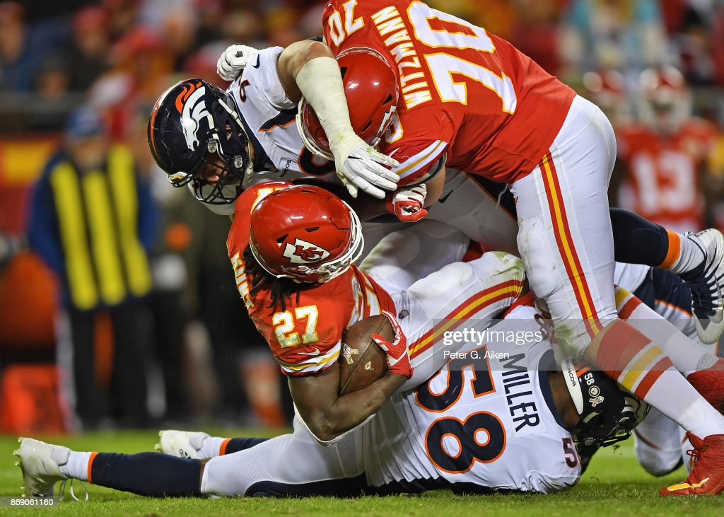 Defenders Adam Gotsis #99 and Von Miller #58 of the Denver Broncos tackle running back Kareem Hunt #27 of the Kansas City Chiefs during the second half on October 30, 2017 at Arrowhead Stadium in Kansas City, Missouri.
