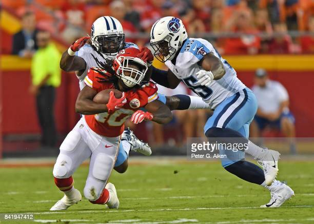 Defenders Da'Norris Searcy and Jayon Brown of the Tennessee Titans tackle running back Devine Redding of the Kansas City Chiefs during the first half...
