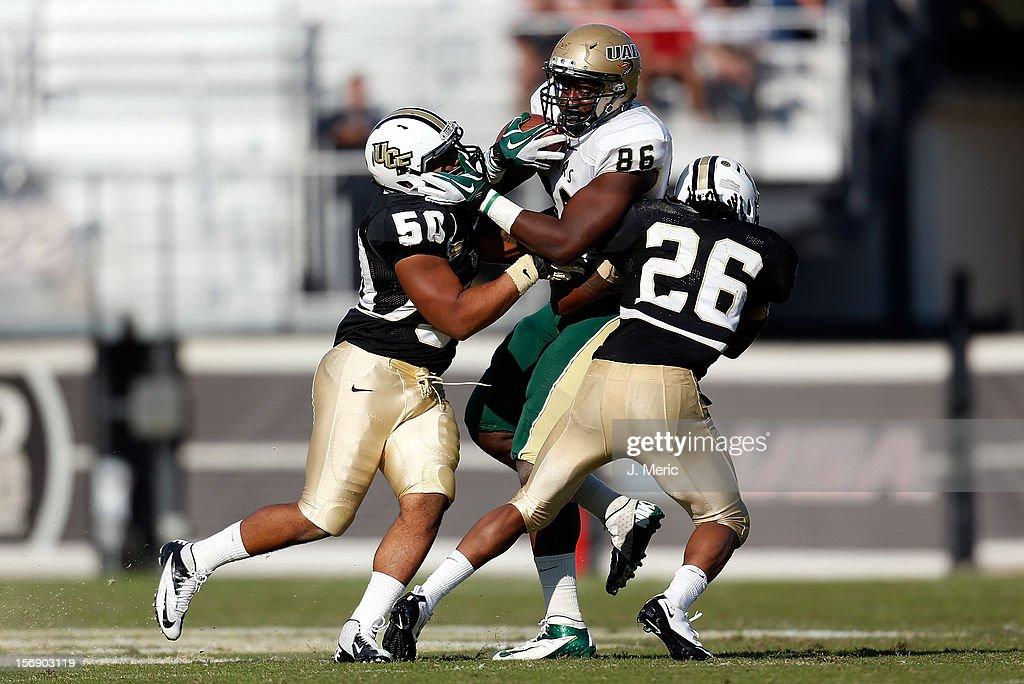 Defenders Domenic Spencer #50 and Clayton Geathers #26 of the Central Florida Knights tackle tightend Kennard Backman #86 of the Alabama Birmingham Blazers during the game at Bright House Networks Stadium on November 24, 2012 in Orlando, Florida.