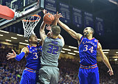 Defenders Perry Ellis and Landen Lucas of the Kansas Jayhawks block the shot of forward Dean Wade of the Kansas State Wildcats during the second half...