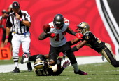 Defenders Roman Harper and Jabari Greer of the New Orleans Saints tackle Arrelious Benn of the Tampa Bay Buccaneers as he fumbles during the game at...