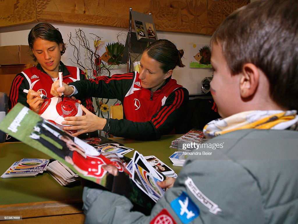 Defenders Sonja Fuss and Annike Krahn of the women's German national soccer team sign autographs on a soccer ball during their visit at an elementary...