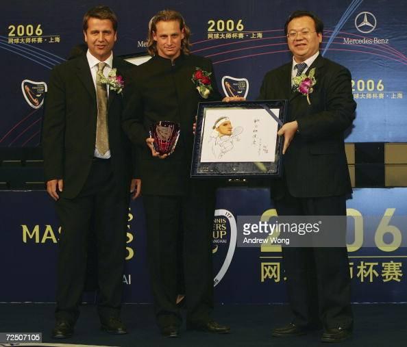 Defending champion David Nalbandian of Argentina receives a souvenir from Chen Jing Director of Minhang District of Shanghai as Brad Drewett Tennis...