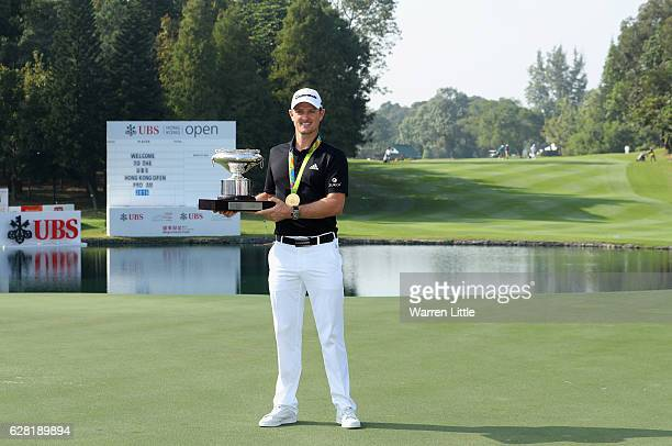 Defending champion Justin Rose of England poses with the UBS Hong Kong Open trophy and his Olympic gold medal ahead of the UBS Hong Kong Open at The...