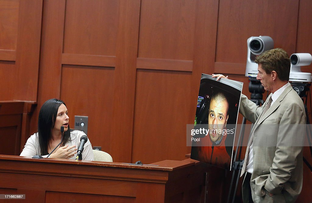 Defense attoney Mark O'Mara shows a photograph of George Zimmerman to witness Jennifer Lauer during Zimmerman's murder trial June 27, 2013 in Sanford, Florida. Zimmerman is charged with second-degree murder for the February 2012 shooting death of 17-year-old Trayvon Martin.