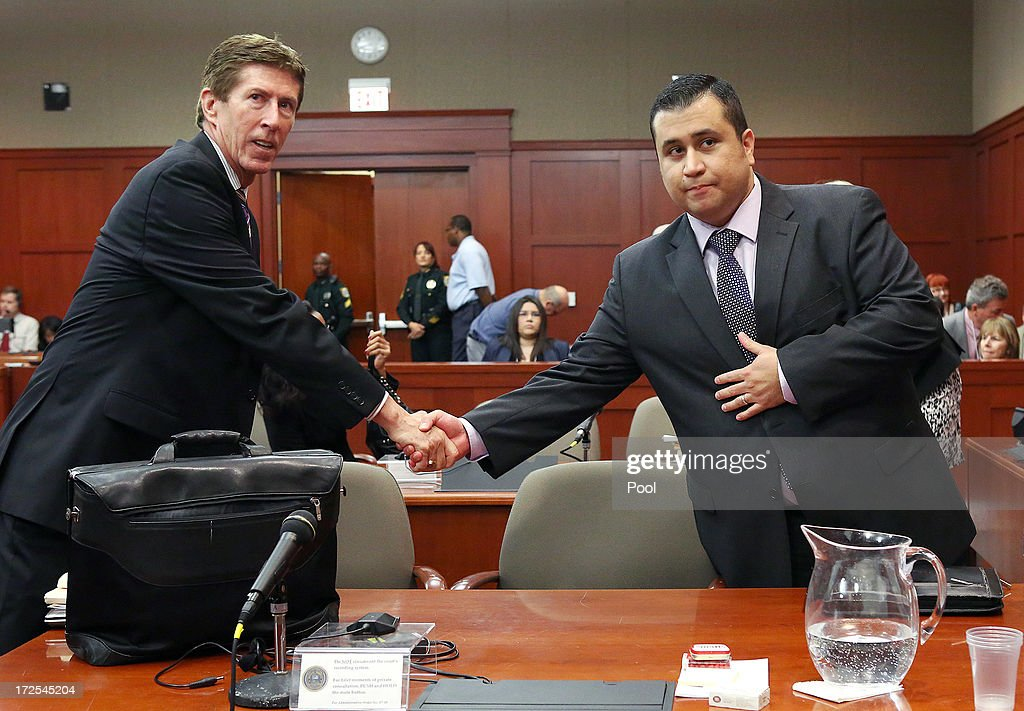 Defense attorney Mark O'Mara, left, and George Zimmerman shake hands at the start of day 18 of Zimmerman's trial in Seminole circuit court, July 3, 2013 in Sanford, Florida. Zimmerman is charged with second-degree murder for the February 2012 shooting death of 17-year-old Trayvon Martin.