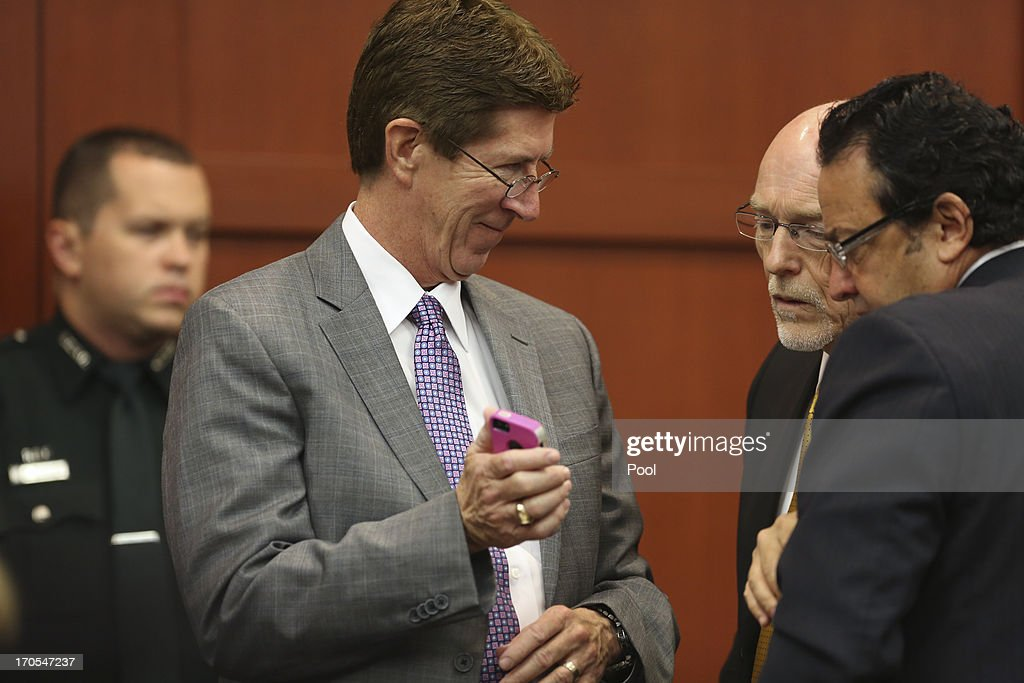Defense attorney Mark O'Mara (L-R) shows co-counsel Don West and jury consultant Robert Hirschhorn something on one of their legal assistant's iPhone during George Zimmerman's trial in Seminole circuit court June 14, 2013 in Sanford, Florida. Zimmerman has been charged with second-degree murder for the February 2012 shooting death of 17-year-old Trayvon Martin.
